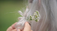 Close up view of stylist putting flowers in model hair Stock Footage