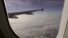 Window view of airplane wing from aboard flight over clouds in sky Stock Footage