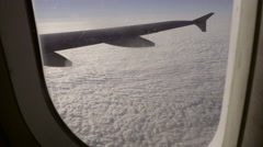 Shaky passenger seat pov of airplane flying over clouds with wing in window view Stock Footage