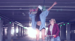 Teen girls having fun at the shopping mall parking, riding in shopping cart Stock Footage