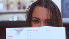 EXTREME CU attractive female hiding her face behind the restaurant menu Stock Footage