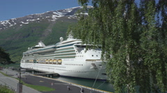 Cruise ship docked in port of Geiranger fjord - Norway Stock Footage