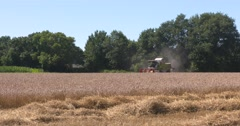Combine harvester in small scale scenic landscape - side view Stock Footage