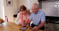 4k, Old couple browsing the internet on their digital tablet and relaxing Stock Footage