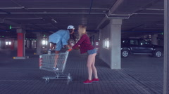 Funny young hipster teen girls riding in shopping cart Stock Footage