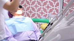 Asian male sitting in dental chair with glasses from ultraviolet Stock Footage