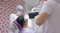 Young male dentist treats patient's teeth using dental unit under supervision of Stock Footage