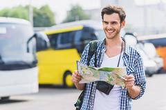 Joyful young man planning his journey Stock Photos