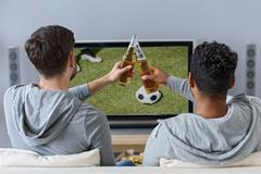 Cheerful male friends entertaining with tv Stock Photos