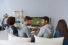 Four young friends entertaining with television Stock Photos