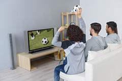 Cheerful friends entertaining with television at home Stock Photos