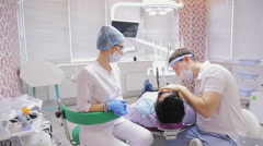 Job of a dentist is paired with a nurse in dental office over lying in a chair Stock Footage