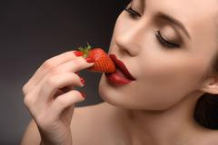 Voluptuous girl eating red berry Stock Photos
