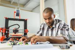 Clever male engineer designing three dimensional printing machine Stock Photos