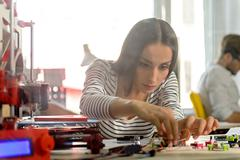 Smart young woman is engineering three dimensional printing Stock Photos