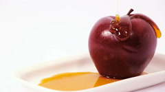 Pouring honey on red apple on white plate with honey isolated on a white Stock Footage