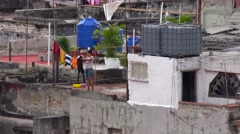 Zoom out from woman doing laundry reveals the skyline of Havana, Cuba. Stock Footage
