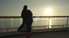 Woman passenger stands on cruise ship open deck at sunset - midnight sun Stock Footage