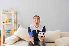 Young adult man watching television Stock Photos