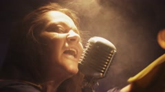 Scrubwoman sing in vintage microphone on stage of club. Dance under spotlight Stock Footage