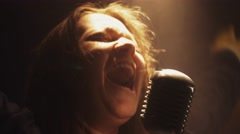 Scrubwoman sing in vintage microphone on stage. Emotions. Smoke. Spotlight Stock Footage