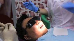 Man with dark hair sits in dental cabinet and waits until end of procedure Stock Footage
