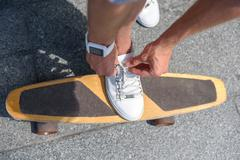 Active man adjusting laces of shoe on skateboard Stock Photos