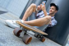 Happy male skater entertaining with smartphone Stock Photos