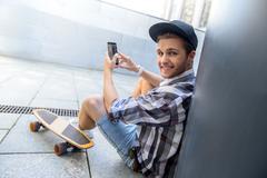 Joyful male skater entertaining with smartphone Stock Photos