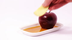 Dipping apple slice in honey on white plate with honey and red apple Stock Footage