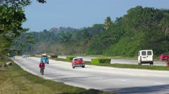 Old cars move along a rural highway in Cuba. Stock Footage