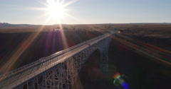 Scenic view flying over bridge spanning gorge under sun Stock Footage