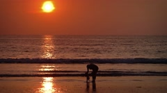 Woman with baby on the beach during sunset Stock Footage