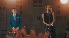 Jazz vocalist in glowing dress and saxophonist in blue suit performing on stage Stock Footage