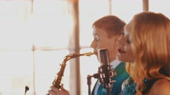 Attractive jazz vocalist dance sing on stage with saxophonist in blue suit Stock Footage