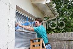 Homeowner Tapes Windows Stock Photos