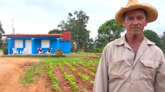 A Cuban farmer stands in front of a farm house on a tobacco farm in Vinales, Stock Footage