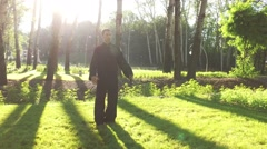 An adult man practicing qigong rotating steel sword around body. Slow motion. 4K Stock Footage
