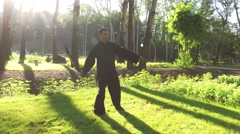 An adult man practicing qigong rotating steel sword around his body. 4K Stock Footage