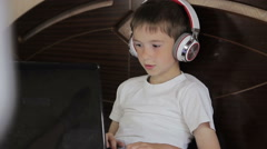 The boy lay listening to music or have an e-learning class using his tablet Stock Footage