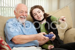 Teen Helps Grandpa with Video Game Stock Photos