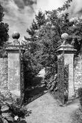 Old wrought iron full size garden gate and brick wall in black and white Stock Photos
