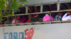 Zoom out from a crowded bus carrying workers to reveal the town of Cienfuegos, Stock Footage