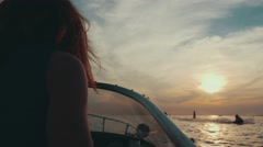 Red hair girl drive motor boat to summer sunset. Romantic evening. Nature Stock Footage
