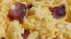 Fried beaten eggs with bacon on plate close-up 4K 2160p 30 fps UltraHD tiltin Stock Footage