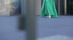 Young girl in green dress walking on the road ahead. Stock Footage