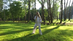Training in a park. Woman practicing qigong rotating steel sword around body. 4K Stock Footage