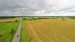 Cars passing driving to the horizon. Green fields and clouds. Aerial footage. Stock Footage