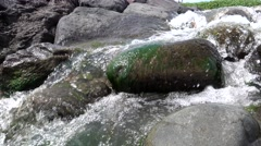 River flowing down on rocks cover with algae Stock Footage