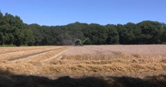Combine harvester in small scale scenic landscape - wide shot Stock Footage